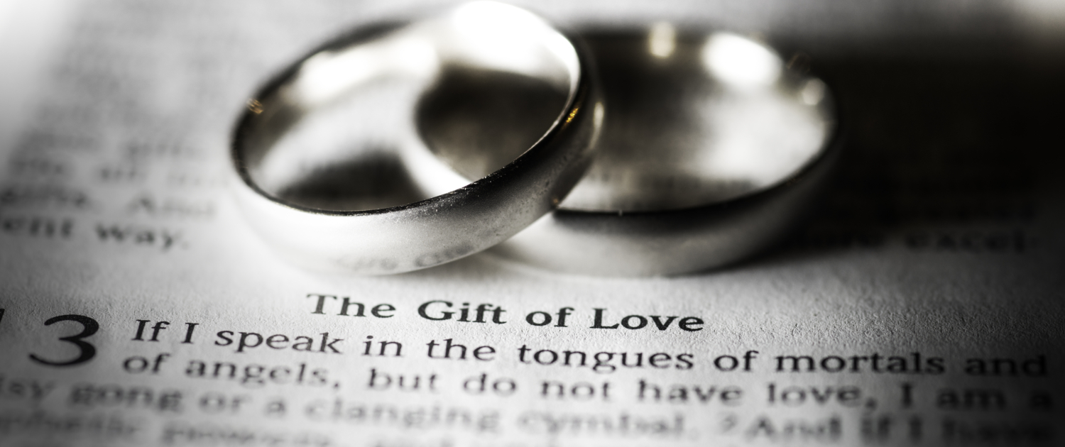 two rings rest by the words 'the gift of love'
