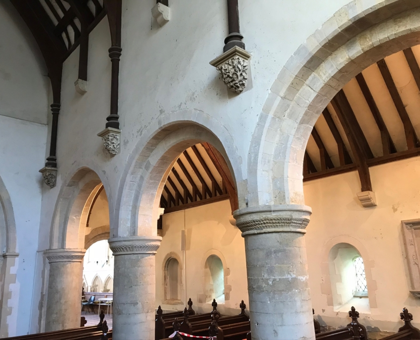 interior of Norman Church with simple arched pillars and wooden beams
